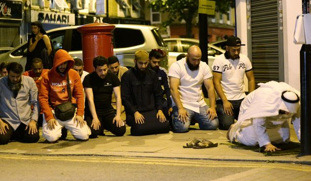 Local people observe prayers after one person died and ten others injured in the terror attack in Finsbury