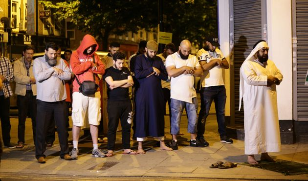 Local people observe prayers at Finsbury Park in north London, where one person has been arrested after...