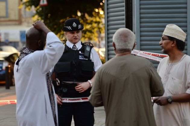 A police officer talks to local people at Finsbury Park in north London, where one man has died, eight...