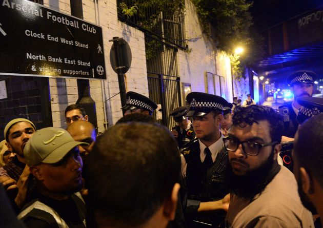 Police officers talk with local people at Finsbury Park following the