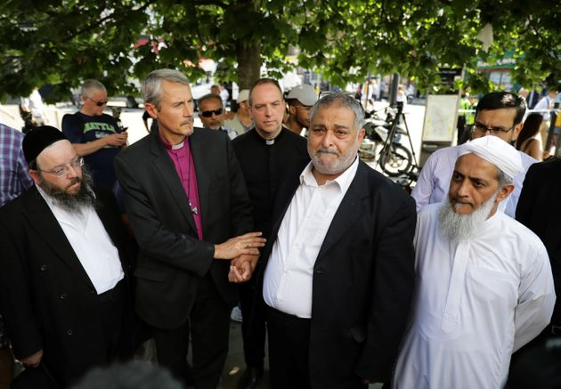 Local faith leaders stand together near the scene on