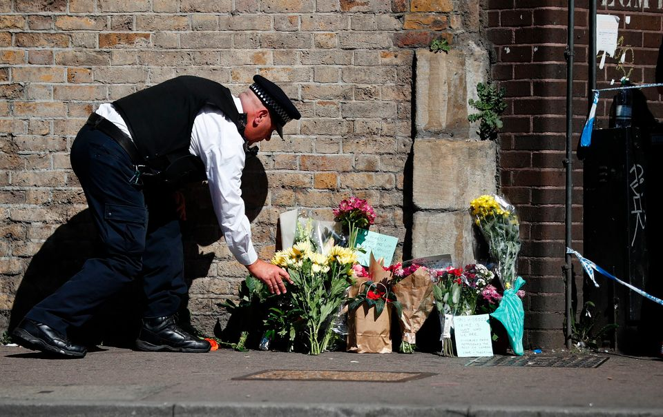 A police officer lays flowers inside a police cordon near the scene in Finsbury Park area of north London after a vehicle was