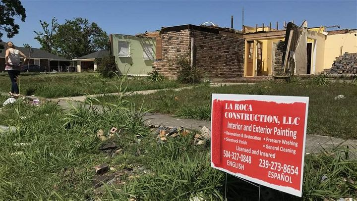 Contractor signs litter the front yards of houses damaged by a February tornado in east New Orleans.