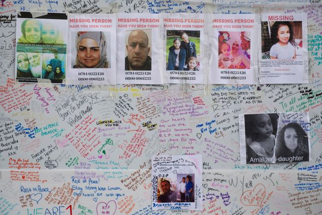 Tributes and missing posters are left on a wall near Latimer Road, close to Grenfell