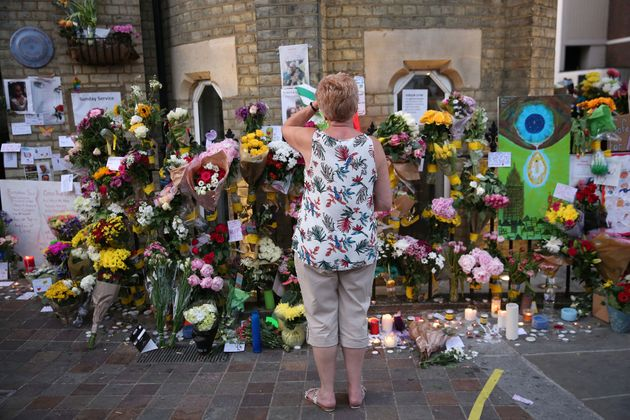 People look at tributes at Notting Hill Methodist Church near Grenfell Tower in west