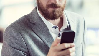 Close up of bearded businessman texting on smart phone.