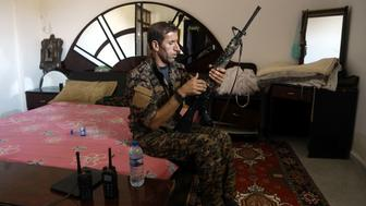 TOPSHOT - A member of the Kurdish People's Protection Units (YPG) sits in a bedroom as he holds a position in the al-Dariya neigbourhood of the Syrian city of Raqa, on June 18, 2017, during an offensive by US-backed fighters to retake the Islamic State (IS) group bastion. / AFP PHOTO / DELIL SOULEIMAN        (Photo credit should read DELIL SOULEIMAN/AFP/Getty Images)