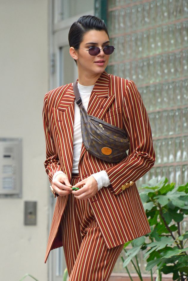 Kendall Jenner wears a modern brown striped suit with white sneakers and her fanny pack while out window...