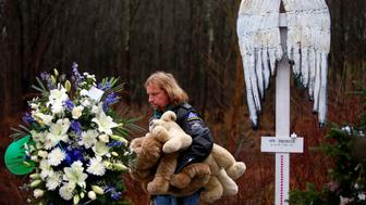 Patrick Carroll holds stuffed animals as he looks at a memorial for the victims of Sandy Hook Elementary School shooting in Newtown, Connecticut December 18, 2012. U.S. authorities continue to investigate the December 14 massacre in Connecticut in which a heavily armed gunman entered Sandy Hook Elementary school and shot and killed 20 children and six adults. The incident, resulting in 28 deaths, including the gunman and his mother, has prompted a fresh debate on U.S. gun control. REUTERS/Joshua Lott (UNITED STATES - Tags: CRIME LAW EDUCATION)