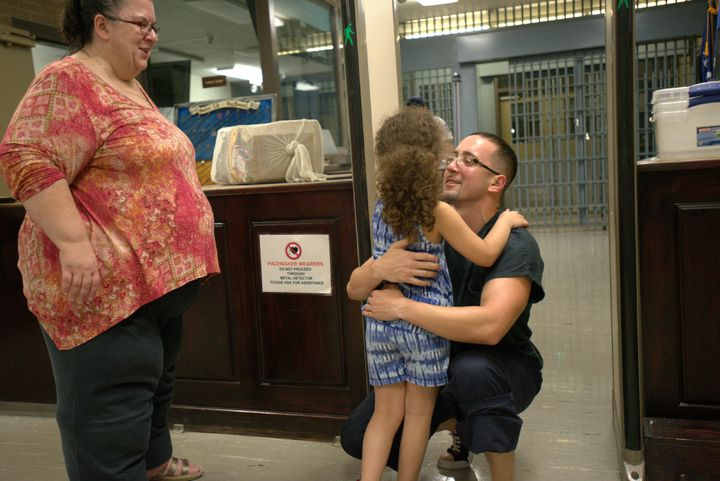 Corey Ladd hugs his daughter, Charlee, while his mother, Lisa, watches.