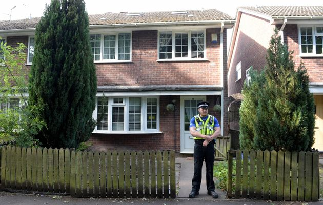 A police community support officer stands at the front of a residence in Cardiff, as searches are being...