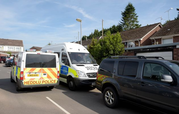 Police vehicles at the rear of a residence in Cardiff, as searches are being carried out in connection...