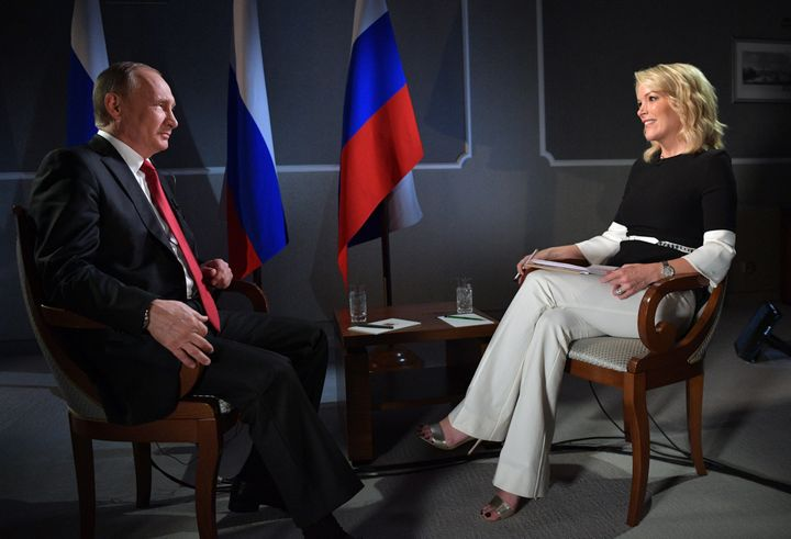 Russian President Vladimir Putin (L) speaks with journalist Megyn Kelly during an interview on the sidelines of the St. Peter