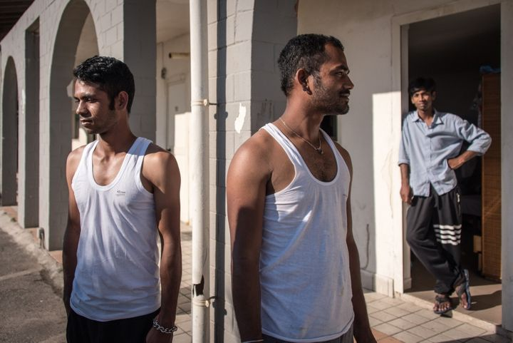 Three Bangladeshi migrants stand outside Hotel Circe, an abandoned building turned into a migrant reception centre, currently