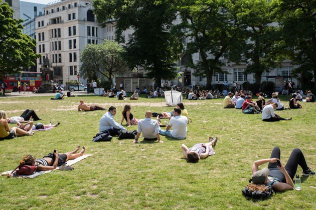 Workers relax in the sun during lunch time in London's Finsbury