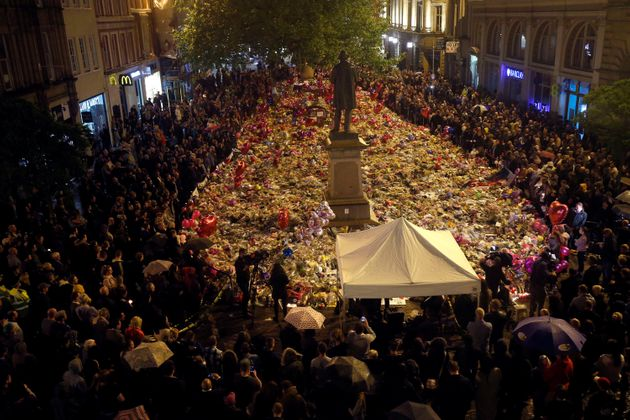 People attend a vigil for the victims of the Manchester