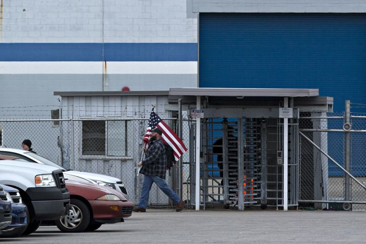A man carries an American flag while leaving an employee entrance outside a Carrier facility in Indianapolis.