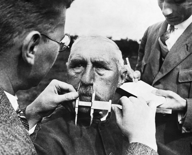 Nazi officials use calipers to measure an ethnic German's nose. The developed a system of facial...