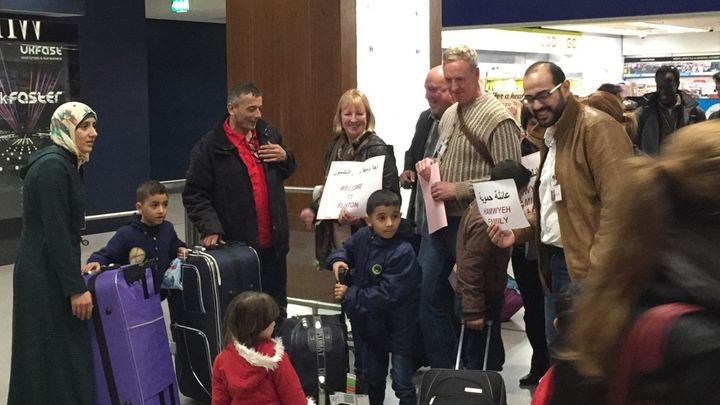 Members of a community sponsorship group in Salford welcome a family of Syrian refugees at Manchester airport