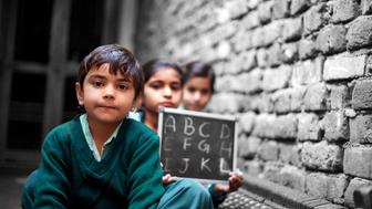 Little School Girls sitting at home near brick wall on Charpai (domestic bed) holding chalkboard wearing school dress and looking to the camera portrait close up.