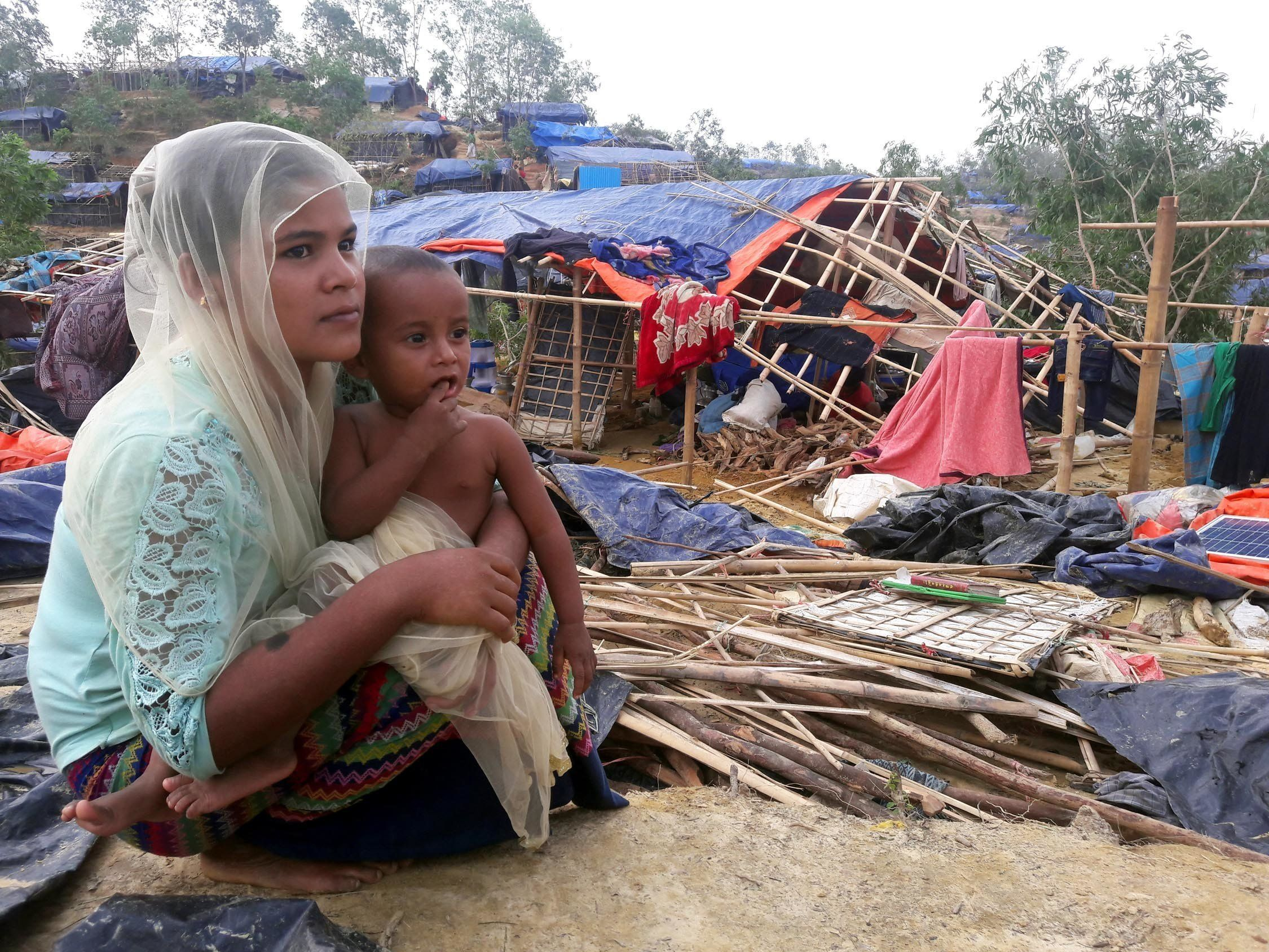 A Rohingya refugee sits near a house destroyed by Cyclone Mora in a camp in the Cox's Bazar district on May 31, 2017. Aid workers warned May 31 of an 'acute crisis' in Bangladesh after a cyclone destroyed thousands of homes and devastated camps housing Rohingya refugees, leaving many without food or shelter. / AFP PHOTO / STR        (Photo credit should read STR/AFP/Getty Images)