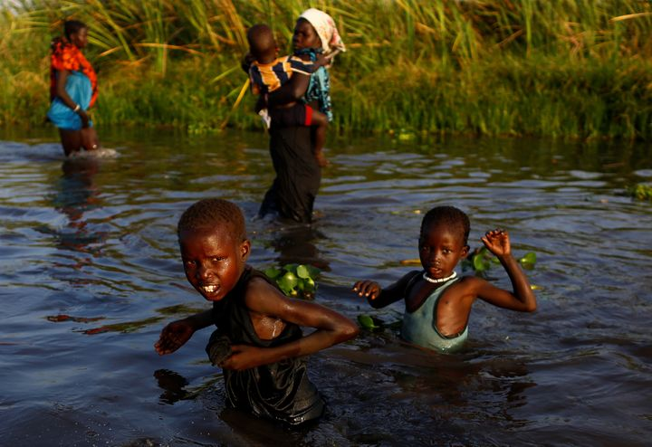 Children cross a body of water to reach a food registration area in South Sudan on Feb. 25, 2017.