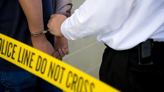 A close-up of a police officer putting handcuffs on a criminal.