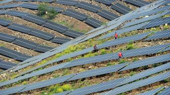Chinese workers check solar photovoltaic modules on a hillside in a village in Chuzhou in eastern Chinas Anhui province on April 13 2017Solar panels which convert sunlight into electricity are a key player in the fast-growing renewable energy sector which also includes water- and wind-generated electricity Unlike energy from fossil fuels such as oil coal and gas the generation of electricity by so-called photovoltaic PV panels does not release planet-harming carbon dioxide