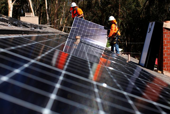 Solar installers from Baker Electric place solar panels on the roof of a residential home in Scripps Ranch, San Diego, Califo