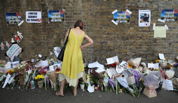 A woman looks at messages at the base of a wall near the scene of an attack next to Finsbury Park Mosque in north London on T