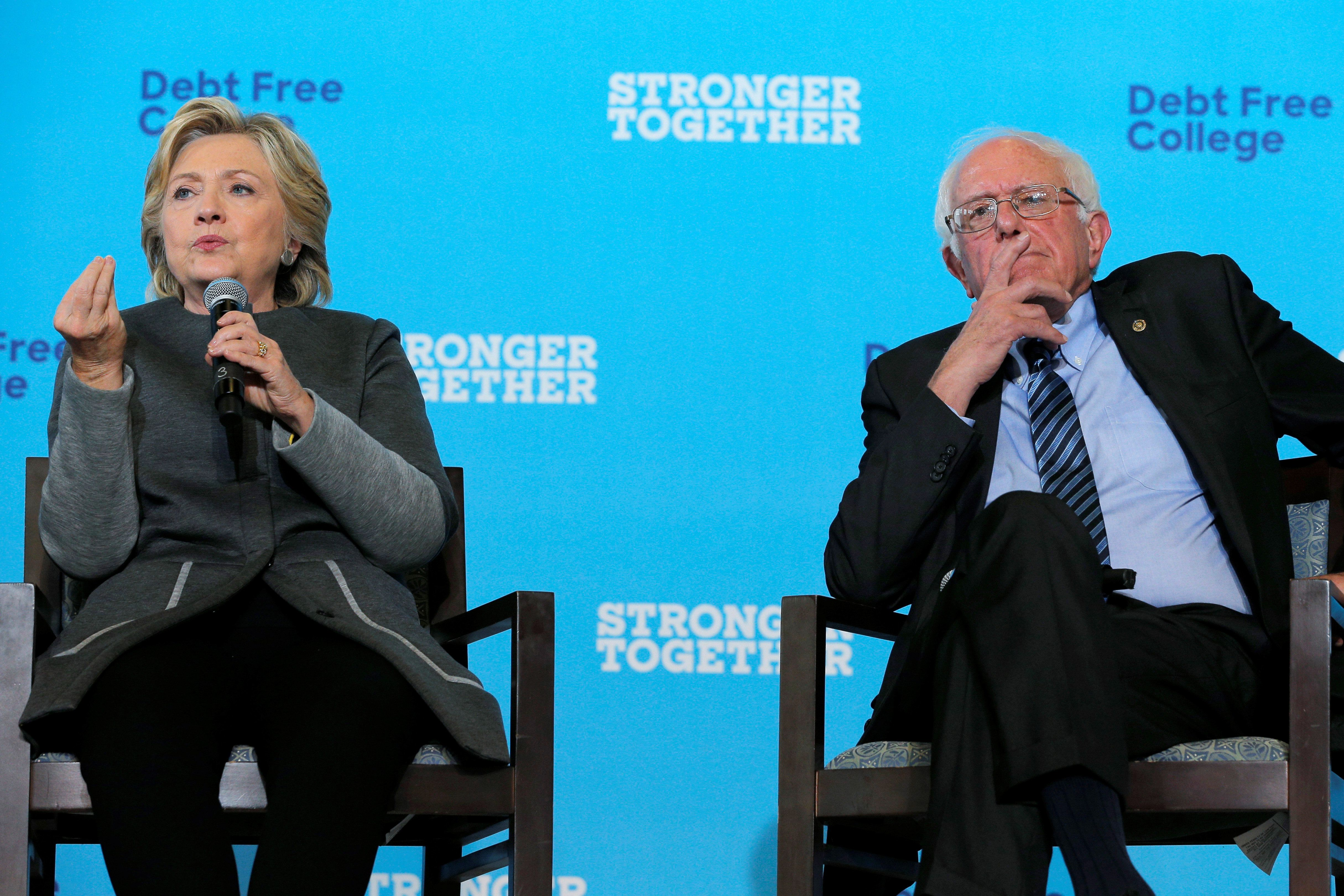 U.S. Senator Bernie Sanders listens as U.S. Democratic presidential nominee Hillary Clinton answers a question about college affordability during a campaign event at the University of New Hampshire in Durham, New Hampshire, United States September 28, 2016.  REUTERS/Brian Snyder