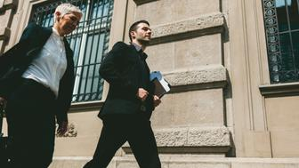 Mature businesswoman and her colleague walking on the street. They are going on business meeting. Woman carrying laptop bag and man carrying papers/documents in his hand.