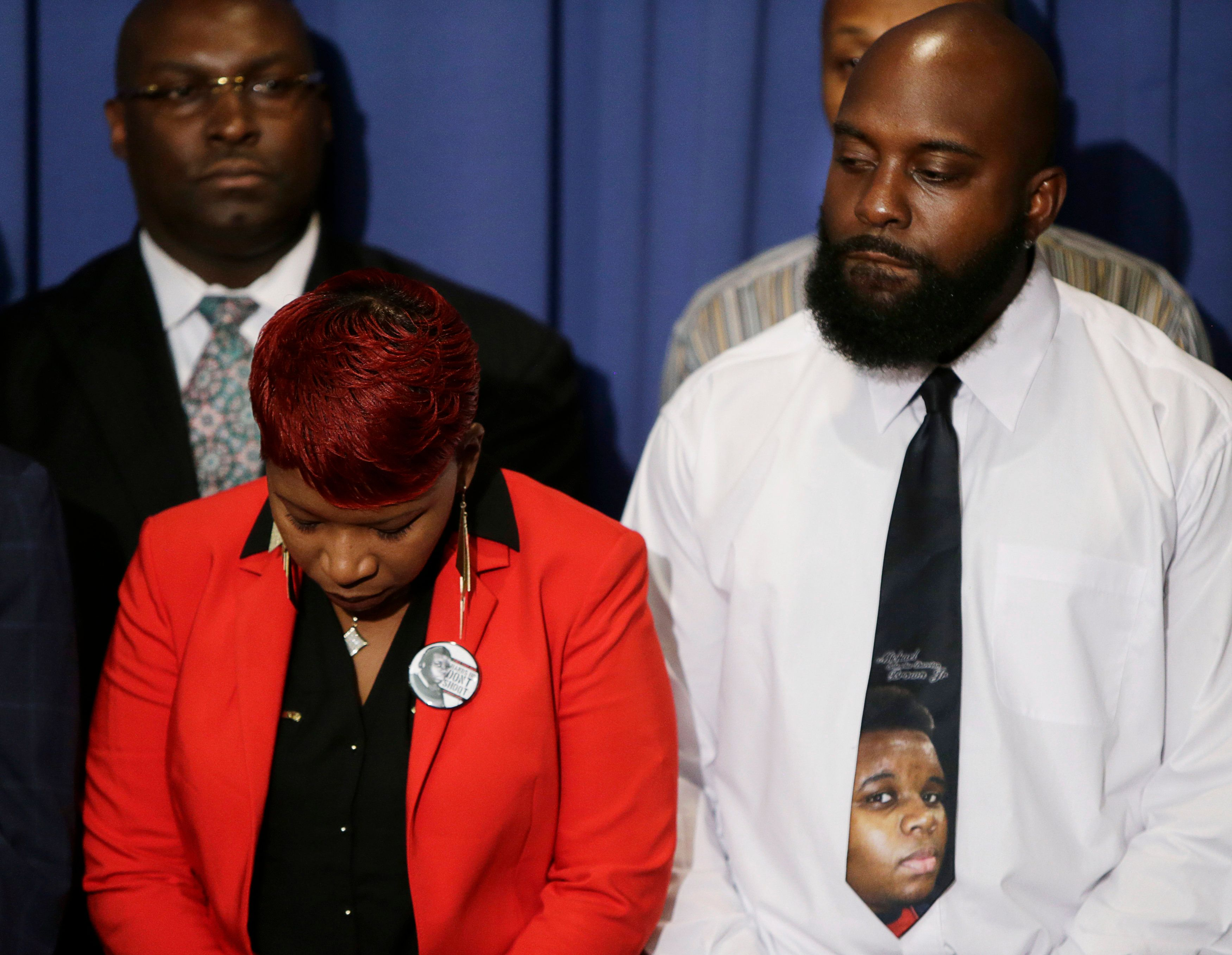 The parents of Michael Brown, Lesley McSpadden (L) and Michael Brown Sr. (R), wear remembrances of their son at a news conference at the National Press Club in Washington September 25, 2014. Five people were arrested and two police officers injured in renewed violence overnight on the streets of Ferguson, Missouri, sparked by a fire that destroyed a shrine to Michael Brown, a teenager killed by a police officer last month. REUTERS/Gary Cameron    (UNITED STATES - Tags: CRIME LAW CIVIL UNREST)