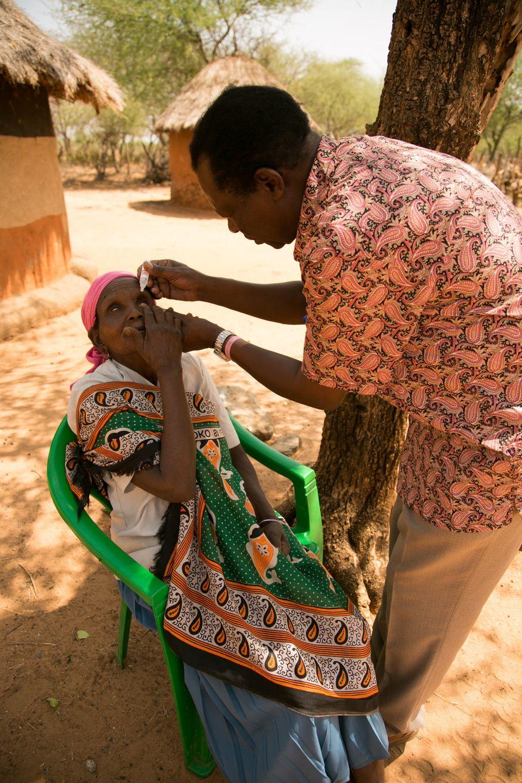 O Dr. Michael Makari aplica colírio nos olhos de Selina Chepserum em consulta de retorno. Makari realiza...