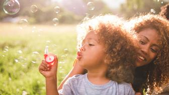Soft glowing sunny moment between a young african-american mother and her cute curly haired baby boy blowing colourful bubbles on the meadow.