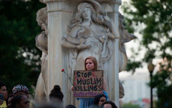 People hold up signs during a vigil in Washington, DC.