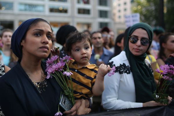 People hold flowers during the vigil in Union Square in New York City.