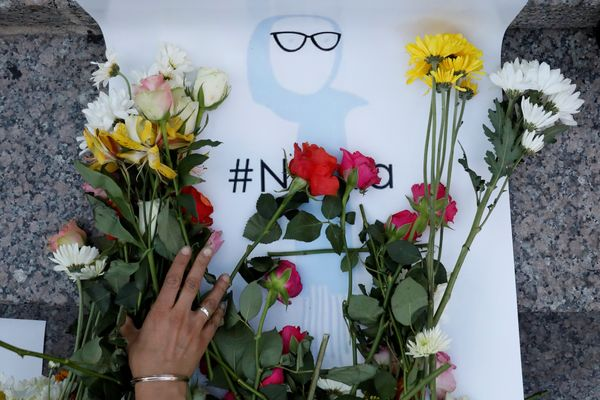 An attendee leaves flowers for Nabra Hassanen, a teenage Muslim girl killed by a bat-wielding motorist near a Virginia mosque