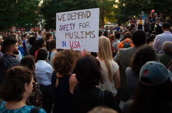 People hold up signs during a vigil in Washington, D.C.