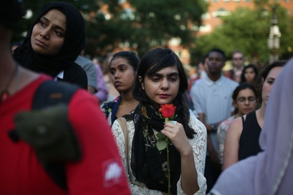 A woman holds a red flower during a vigil in Union Square in New York.