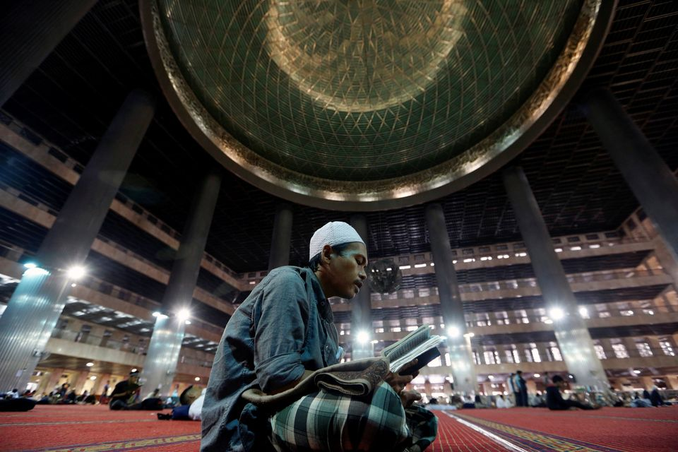 A Muslim man reads the Koran while waiting for the Iftar (breaking fast) meal during the last week of the holy fasting month