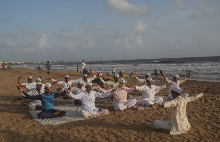 On the eve of World Yoga Day Mumbai's Dabawala celebrated by doing yoga exercises at Versova beach.