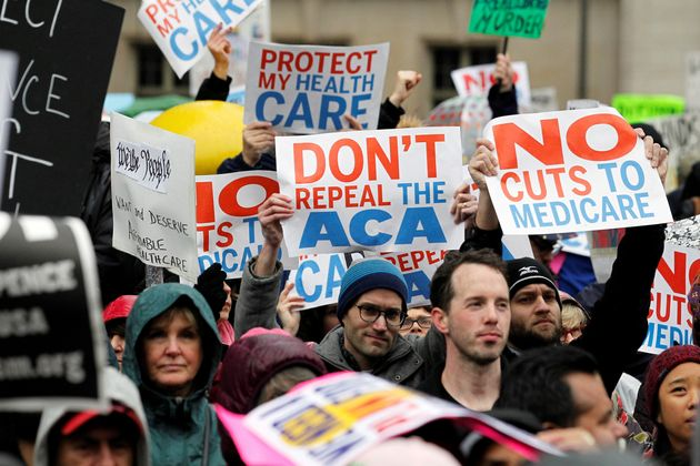 Demonstrators hold signs in support of Obamacare near a Philadelphia hotel where Republican lawmakers...