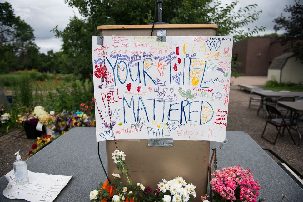 "A sign reading ""Your Life Mattered"" hangs on a podium outside J.J. Hill Montessori School on July 14, 2016, in Saint Paul, Mi"