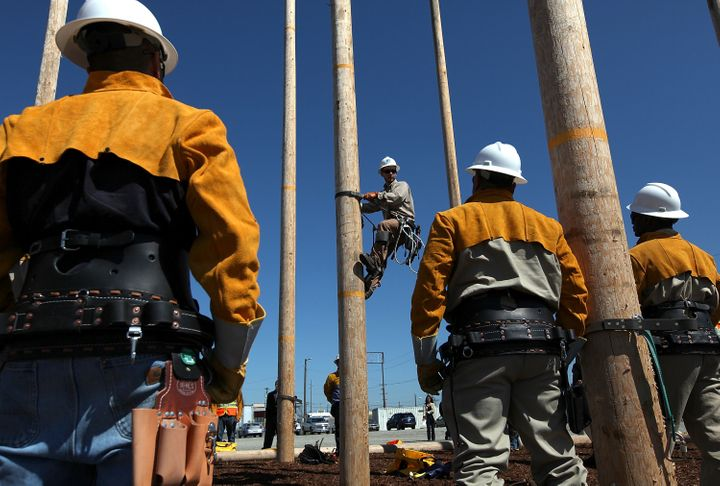 Students watch a Pacific Gas and Electric instructor navigate a utility pole during a training course for the utility industr