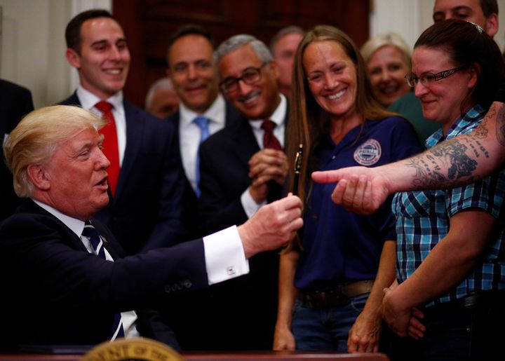 "Trump hands a pen to Charles Robel after delivering remarks on ""Apprenticeship and Workforce of Tomorrow"" initiatives at the"
