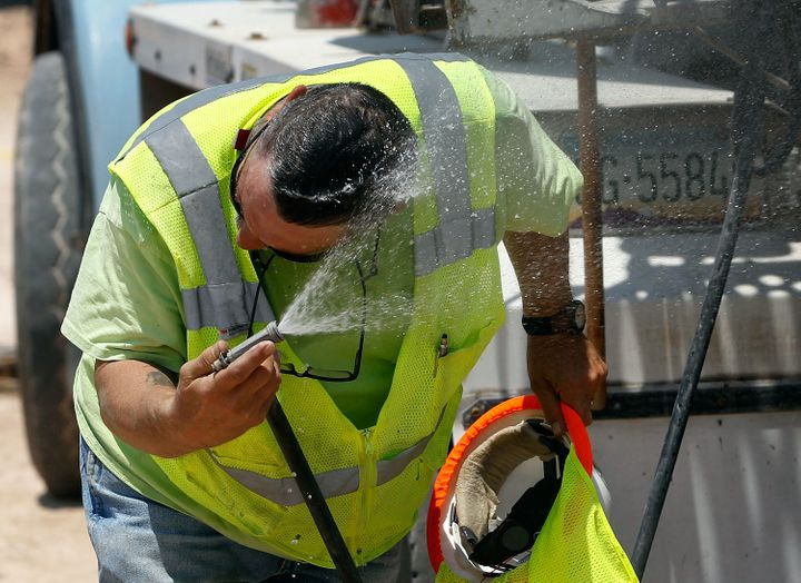 A Phoenix area cement truck operator uses a water hose to cool down. Temperatures have reached 120 degrees in the southwest t
