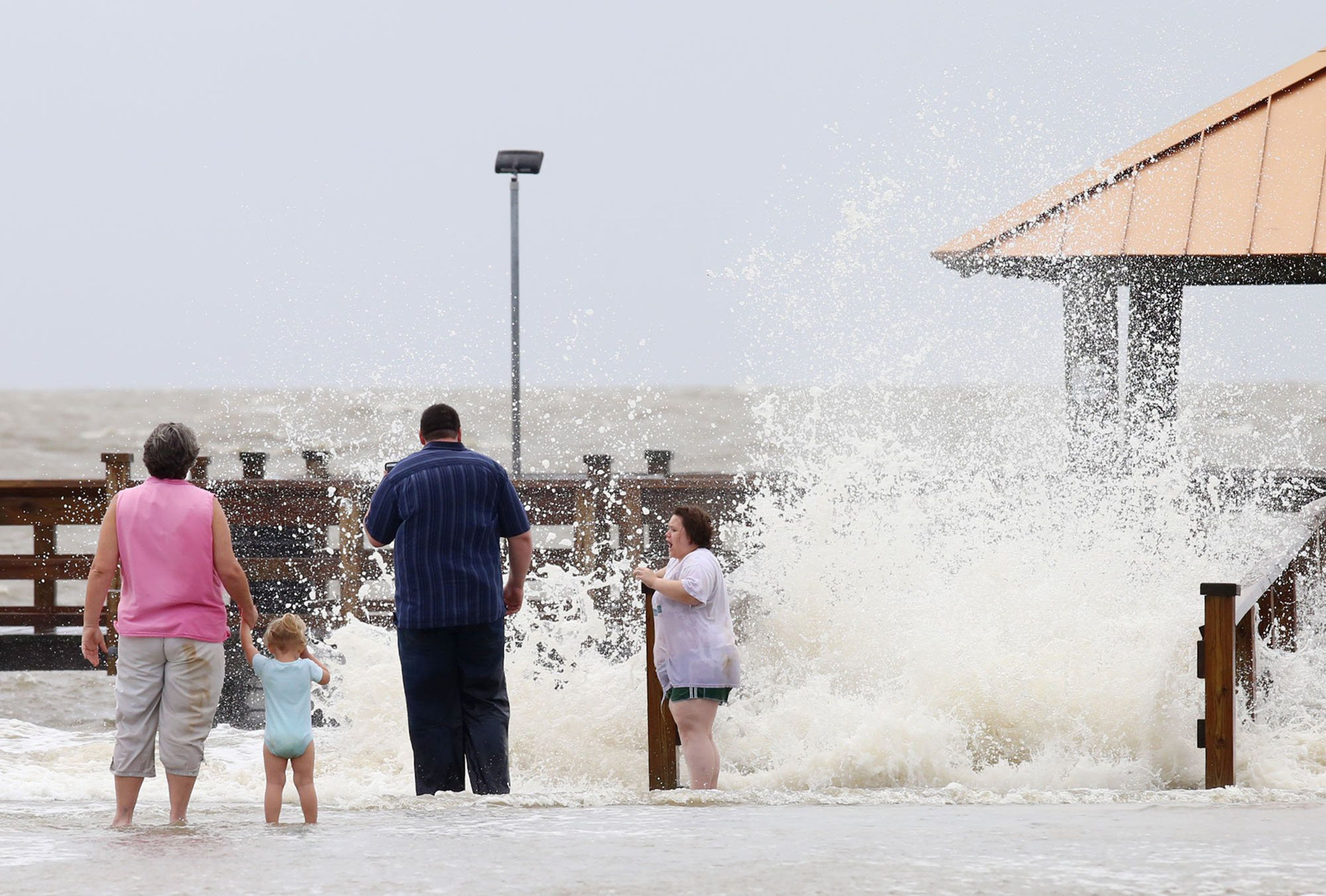 Kathy Majors and her granddaughter, Chloe Schlunaker, 2, and her parents, Justin and Heather Schlunaker of D'Iberville, watch as waves crash against the shore at Moses Pier in Gulfport on Wednesday, June 21, 2017 as Tropical Storm Cindy moved through the area. The family recently moved to the coast from Laurel and wanted to see the storm up close. (John Fitzhugh/Biloxi Sun Herald/TNS via Getty Images)