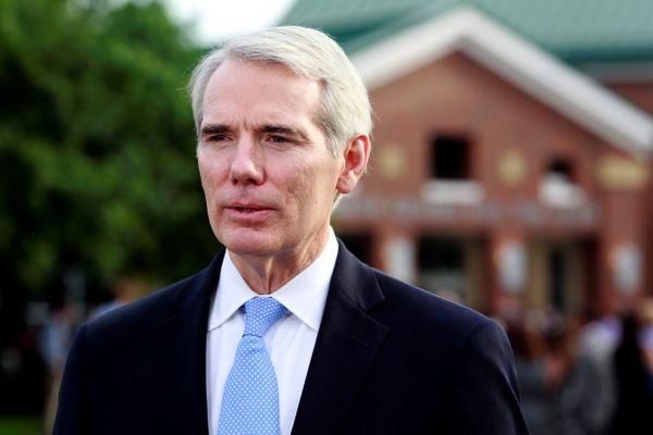 Sen. Rob Portman (R-Ohio) talks to reporters outside the high school.