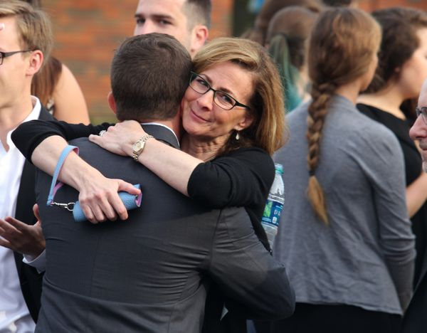 Mourners hug one another outside the funeral.